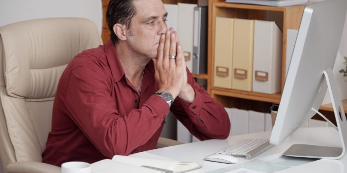 Mature businessman with a problem at the office sitting at his desk with frowning at his computer screen